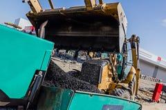 Transport hot asphalt into bulldozer scoop to the spreader machi Stock Photos