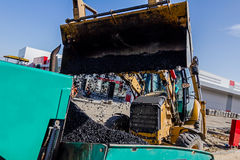 Transport hot asphalt into bulldozer scoop to the spreader machi Royalty Free Stock Images
