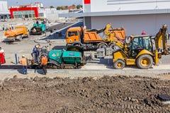 Transport hot asphalt into bulldozer scoop Stock Photos