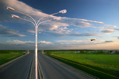Transport Landscape. Airplane flying over highway. Lamp on the foreground Royalty Free Stock Image