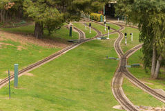 Transport. A mini railway track at the gardens of a park with trees and shed and signals Royalty Free Stock Images