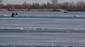 Transport for movement on the ice. Winter, two men in a boat. Crossing in the winter on the river. stock video