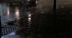Transport on the road at rainy night. Nasty weather in night city. Heavy rain pouring while cars and motorcycles driving along the road stock video