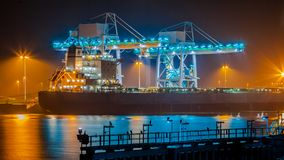 Transport Ship in harbor at night. Transport ship on a wharf during twilight is unloaded with huge modern cranes under colorful lighting Royalty Free Stock Image