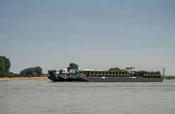 Transport ship loaded with tractors and trucks driving downstrea Royalty Free Stock Photo