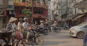 Transport traffic by roadside cafe in Hanoi, Vietnam. HANOI, VIETNAM - OCTOBER 27, 2015: Road traffic with domination of motorbikes in city street with houses stock video