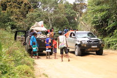 Transport and traveling in Papua mountains. Papuan families with litlle kids standing on road around cars full of goods and waiting for transport in jungle and stock photography