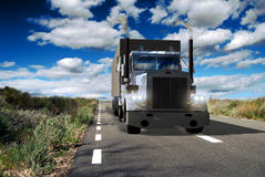 Transport truck. A transport truck running on road in spring under a cloudy deep blue sky Stock Photos