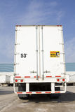 Transport truck from behind. Shot in yard with other trucks and warehouse in the background Royalty Free Stock Images