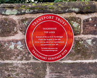 "Transport Trust Heritage Plaque, Worcester and Birmingham Canal. Transport Trust Heritage Plaque or ""Red Wheel"" on the wall by the top lock on the famous Stock Image"