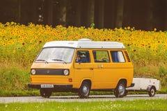 Transportador de Volkswagen del vintage delante de un campo con la floración Imagenes de archivo