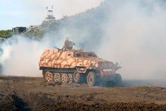 Transportador militar, tipo pesado, algum fumo da guerra. Imagens de Stock