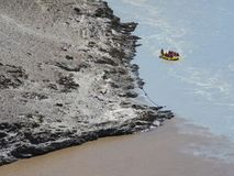 Transportando em um rio da montanha, na afluência de dois córregos, um barco amarelo inflável pequeno apressa-se abaixo da água Fotos de Stock Royalty Free