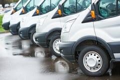 Transportando a empresa de serviços camionetes de entrega comerciais na fileira Fotografia de Stock