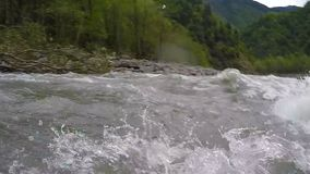 Transportando en balsa con las ondas, las rocas grandes y los peligros requiriendo maniobrar exacto almacen de video