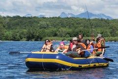 Transportar do verão: grupo de turistas e de viajantes que flutuam no rio na jangada Fotos de Stock
