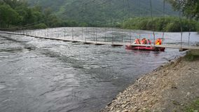 Transportar el barco en balsa flota debajo de puente colgante peligroso bajo de la ejecución sobre el río metrajes