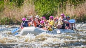 transportar Empresa alegre dos povos das idades diferentes que navegam em um barco inflável de borracha teamwork Emoções positiva imagem de stock
