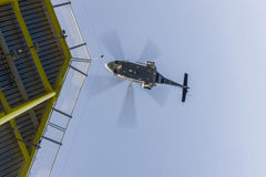 Transportation. Aviation transportation. View from bottom of blurred commercial helicopter from onshore approaching oil and gas platform helideck to pick up royalty free stock photo
