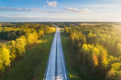 Transportation background. Free road to horizon. Aerial autumn landscape with blue sky and sunny forest. High way with new cover royalty free stock photo