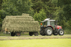 Transportation of bales of hay. With a red tractor and flat car Stock Photography
