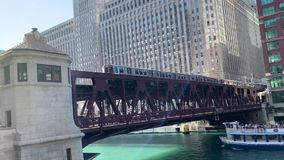 Transportation in Chicago with elevated `el` train crosses the Chicago River on the Wells Street track, and tourboat crosses under stock footage