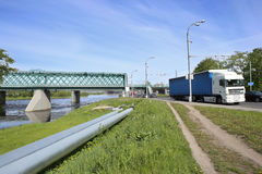 Transportation in city: railway bridge, industrial pipes and road transport. Stock Image