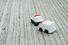 Transportation concept - cute police car and ambulance van toy model. On concrete road Royalty Free Stock Photo