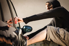 Transportation and crime- thief breaking car lock. Transportation, crime and ownership concept - thief breaking the car lock royalty free stock photo