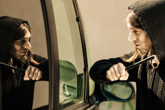 Transportation and crime- thief breaking car window Stock Photography