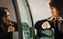 Transportation and crime- thief breaking car window Stock Image