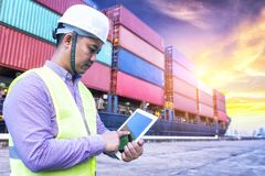Transportation engineer working at port. Use digital tablet with container import and export background royalty free stock photography