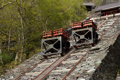 Transportation incline. Two trolleys with crates of cut slate on rails on a steep slate made incline Stock Photos