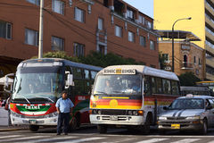 Transportation in Lima. Lima, Peru - September 13, 2011: Buses and a taxi standing at red light with a bus conductor standing on the street calling out for Royalty Free Stock Photography