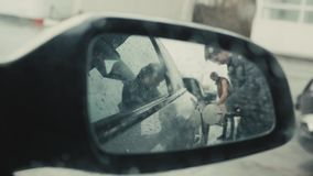 Transportation and ownership concept - man pumping gasoline fuel in car at gas station, view from mirror, rainy day. Transportation and ownership concept - man stock video footage