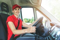 Transportation Services - Young Female Driver In Red Uniform Driving A Van. Smiling At Camera Stock Photo