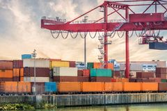 Transportation, shipping and logistics concept. Crane and many containers in harbour at sunset.  Royalty Free Stock Image