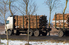 Transportation of timber. Delivery truck carries wood to the sawmill Royalty Free Stock Photo