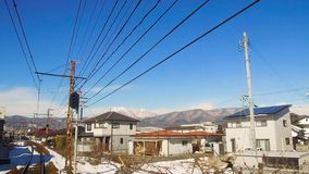 View to suburb from train or railway in Japan. Transportation and travel concept - view to suburb of Nagano from moving train or railway in Japan stock video footage