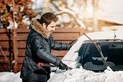 Transportation, vehicles, winter, people concept - man cleaning car from snow during cold sunny day royalty free stock image
