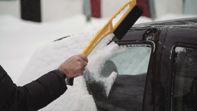 Transportation, winter, weather, people and vehicle concept - man cleaning snow from car with brush in living house stock video