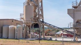 Transportband en van de opslagtank structuren in concrete productiefaciliteit stock fotografie
