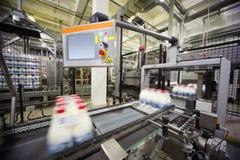 Transportband met verpakte melkflessen bij fabriek Stock Foto