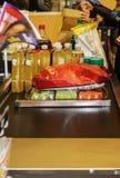 Transportband som fylls med mat på livsmedelsbutikmarknaden med säckar som fylls upp, och unidentifiable kunder som får klara att arkivfoton
