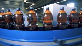 Transportband som transporterar plast- flaskor som fylls med öl stock video