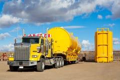 Transporte amarillo con los tanques del campo petrolífero Imagen de archivo libre de regalías
