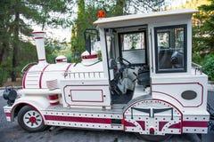 Transporte branco do turista sob a forma de um trem do brinquedo Transporte do divertimento foto de stock