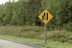 Transporte Canadá de Quebeque do preto do amarelo do cargo de sinal da estrada estreita na frente da floresta fotos de stock