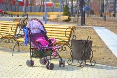 Transporte de bebê vazio no parque da cidade perto do banco Perto do balde do lixo fotografia de stock royalty free