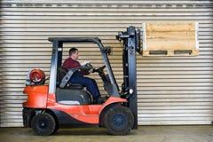 Transporte de la carretilla elevadora un rectángulo de madera Imágenes de archivo libres de regalías